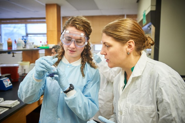 KATHERINE BELL '19 (CLAS), LEFT, AND  NICHOLE BRODERICK  – ASSISTANT PROFESSOR OF MOLECULAR AND CELL BIOLOGY – LOOK AT VIALS OF COLLECTED BACTERIA. (PETER MORENUS/UCONN PHOTO)