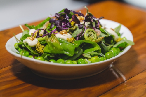 Our spring salad features fiddlehead ferns, peas, pickled ramps, mustard seeds, and opal basil, among other green goodies.