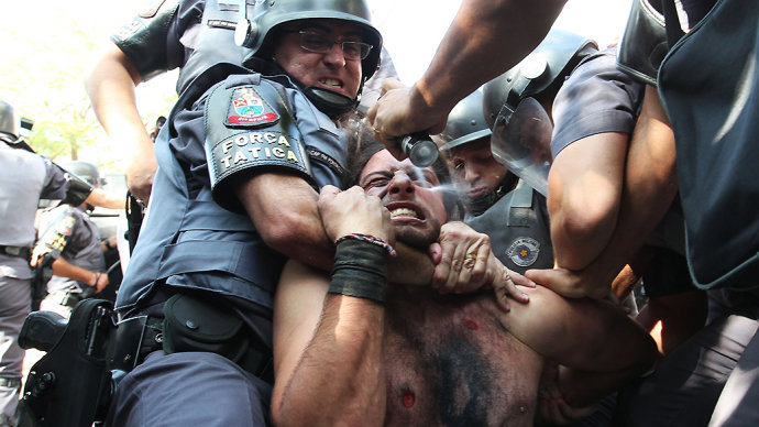 Brazilian police spraying immobilized civillian. Photo by Robson Fernandes.