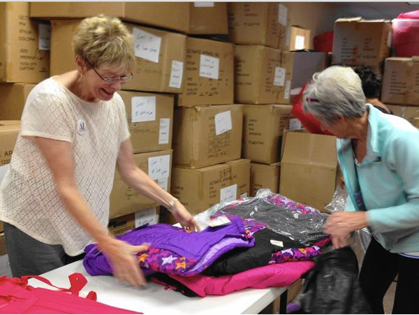 Pat Allen and Judy Casten pack coats for school children in this 2014 photo