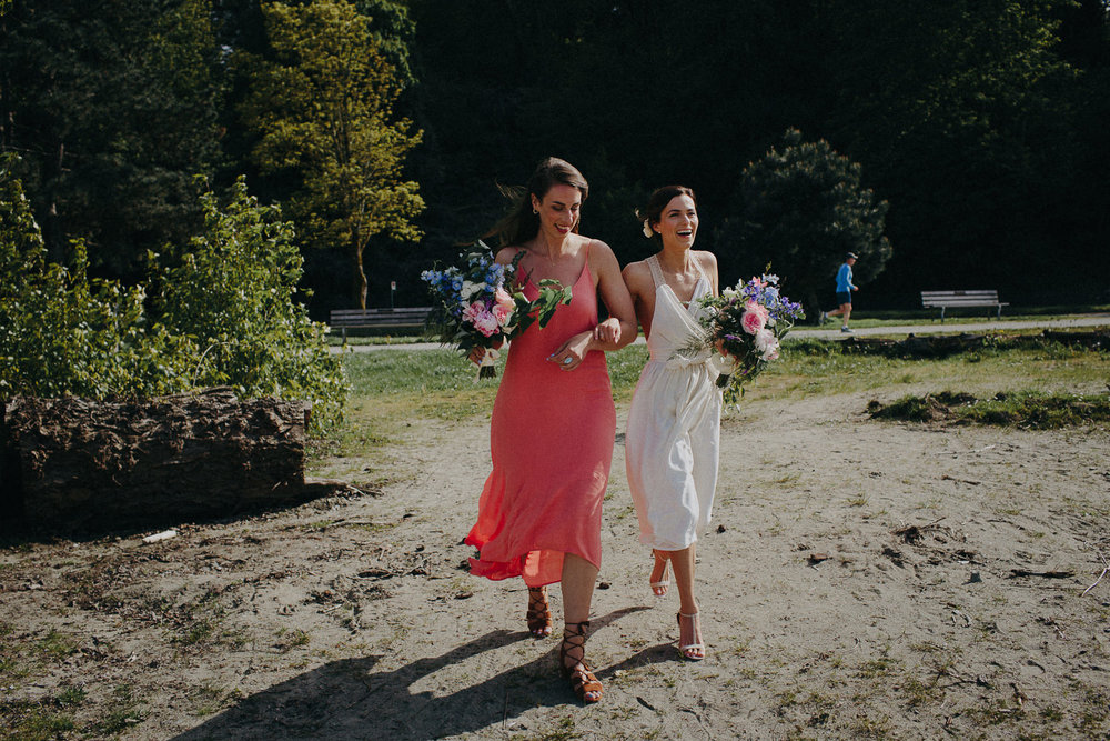 bride and maid of honor walking on beach