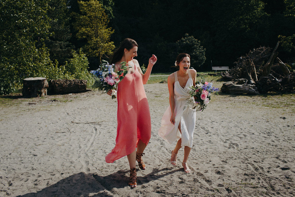 bride and maid of honor laughing on the beach