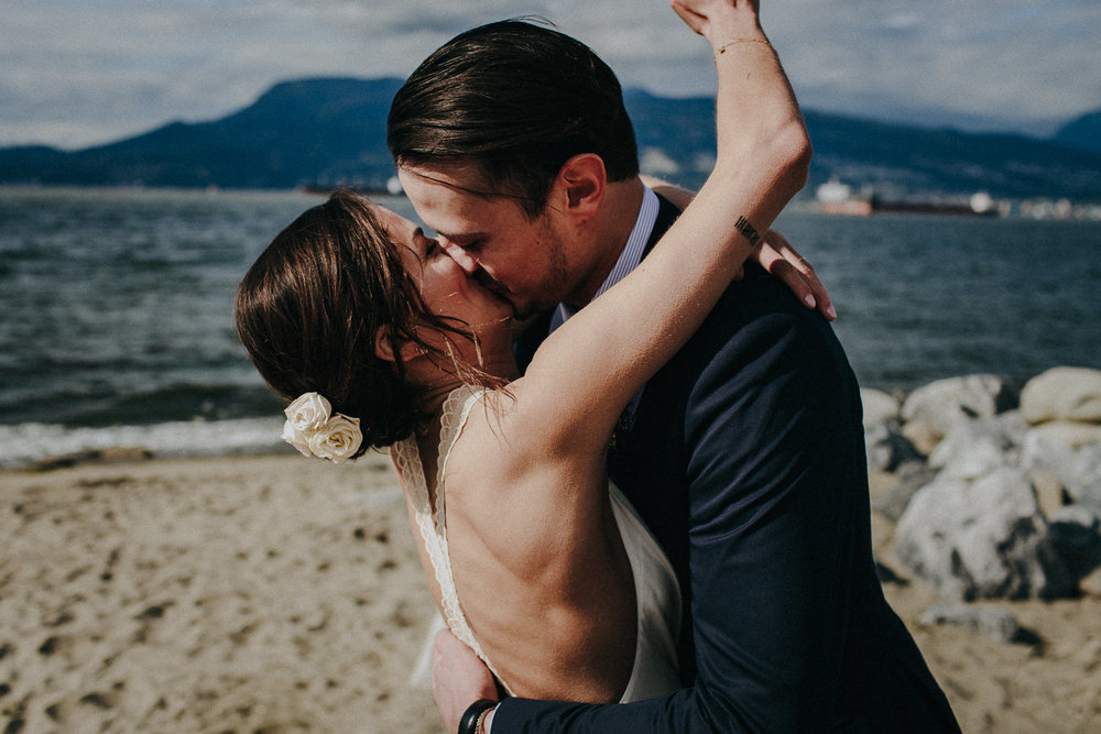 bride and groom kiss at spanish banks