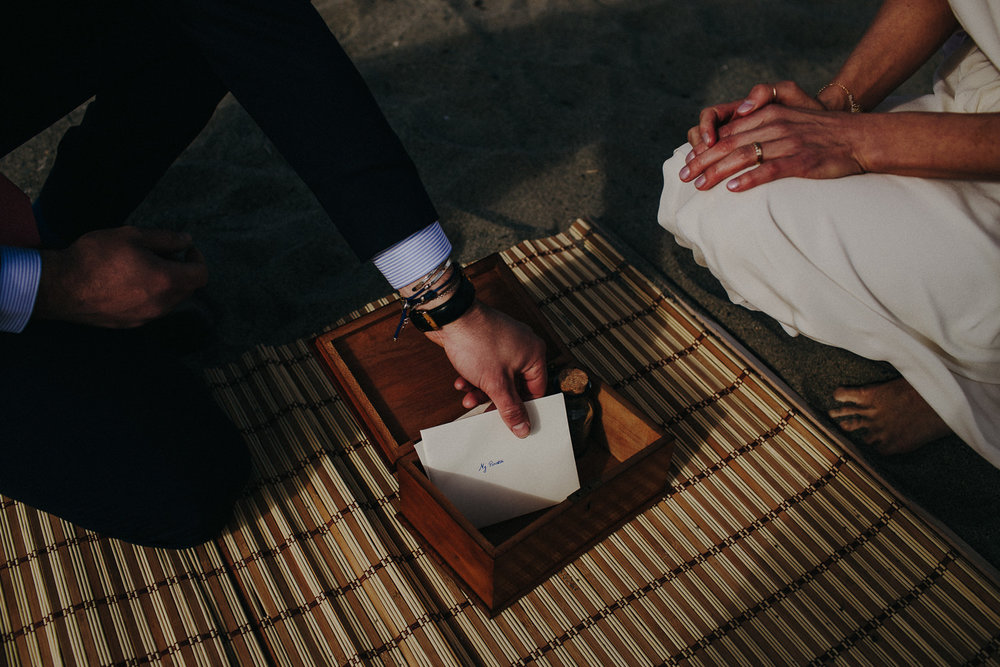 groom putting a love note in a box