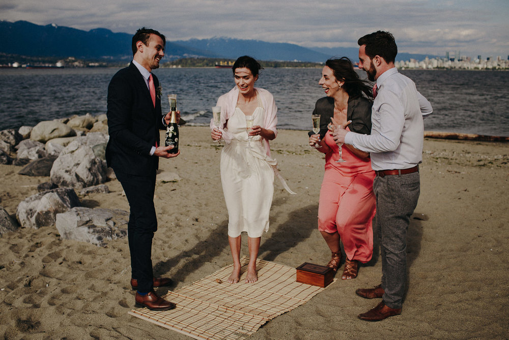 the wedding party enjoying champagne on the beach