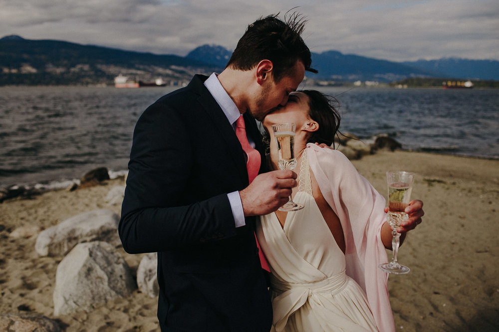 the groom kisses the bride with champagne in hand