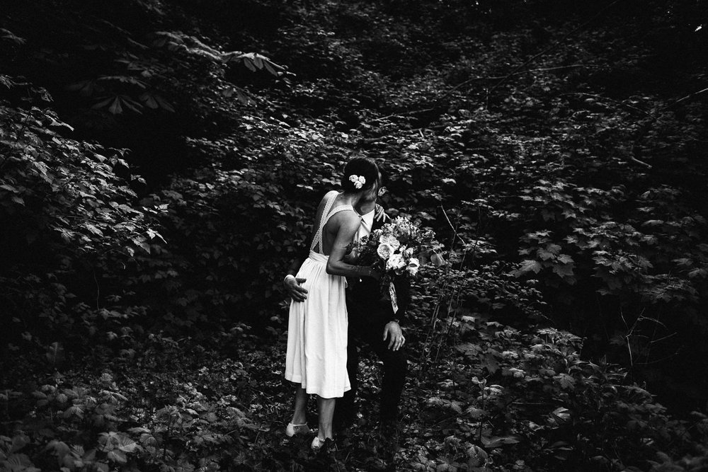 bride kissing the groom in the trees