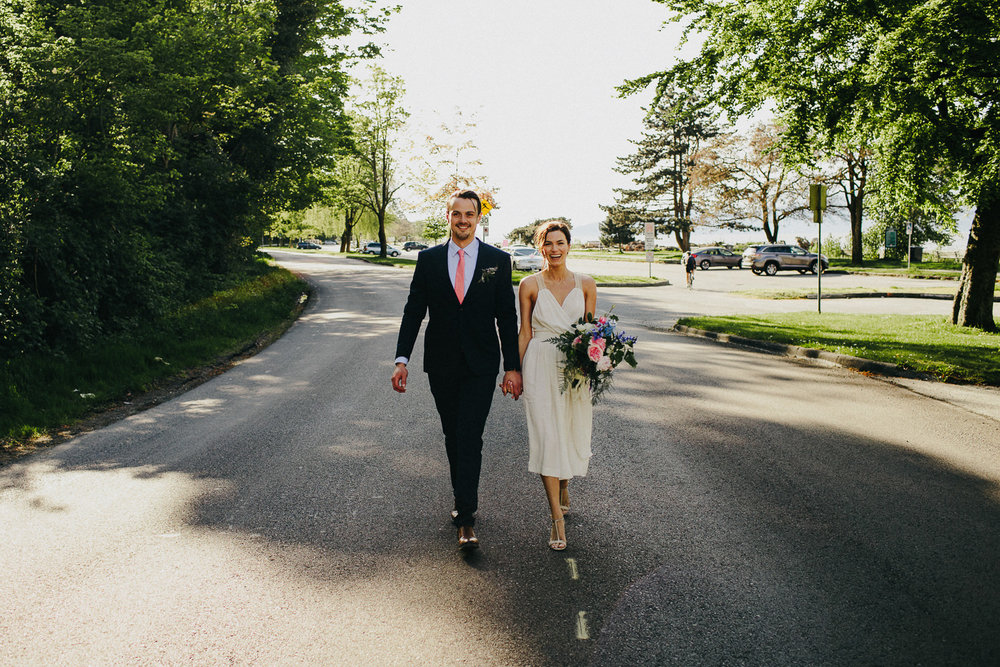 bride and groom walking on a road in kitsilano