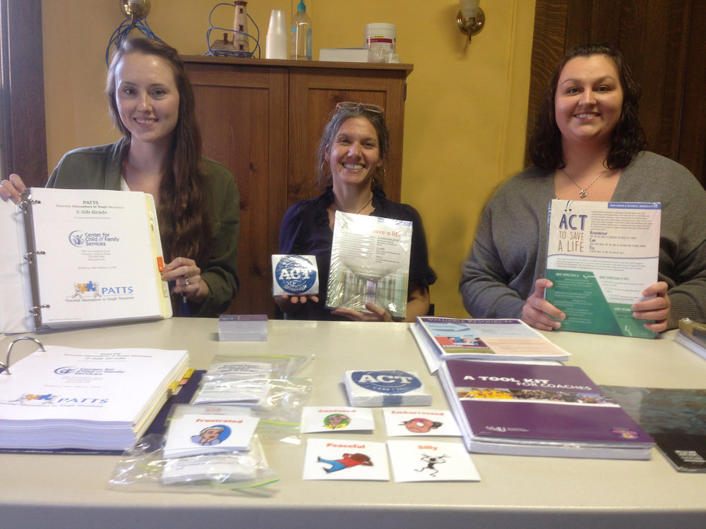 Youth Health Service Tucker County Team members are pictured showing new curriculum materials purchased through grant funds.  Pictured left to right:  Therapist Emily Medlock, Therapist and Team Leader Anne Farmer, and Family Service Specialist Samantha Mollohan.