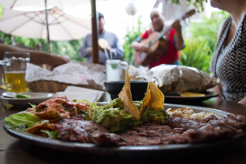 Carne Tampiquena plate with a side of a serenade at La Estancia restaurant. This dish includes a thin slice of grilled steak,a cheese enchilada covered in red sauce, grilled onions, tortilla soup, house salad, and guacamole.
