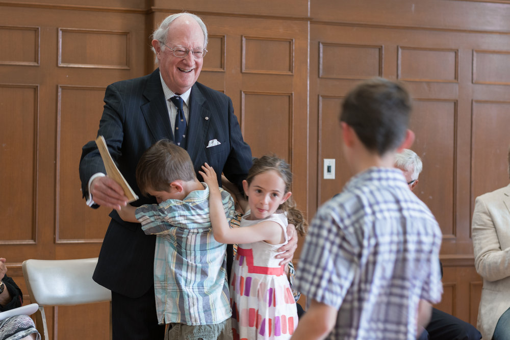 University of King's College president George Cooper is greeted by his grandchildren with hugs at his portrait unveiling.