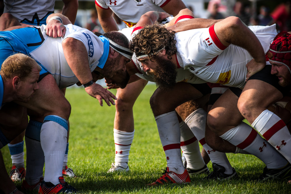 Players stare each other down at a scrum at the 2015 Battle for New Scotland, an international rugby match between Rugby Canada and Glasgow Warriors.