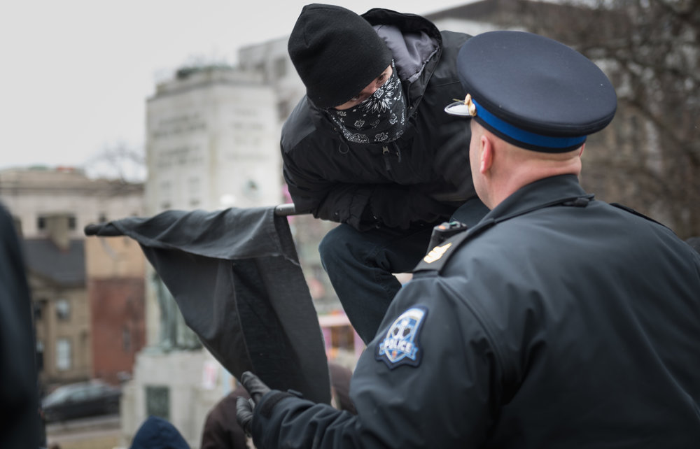 A terse exchange of words takes place between a police officer and an anarchist at the Halifax march on Washington.