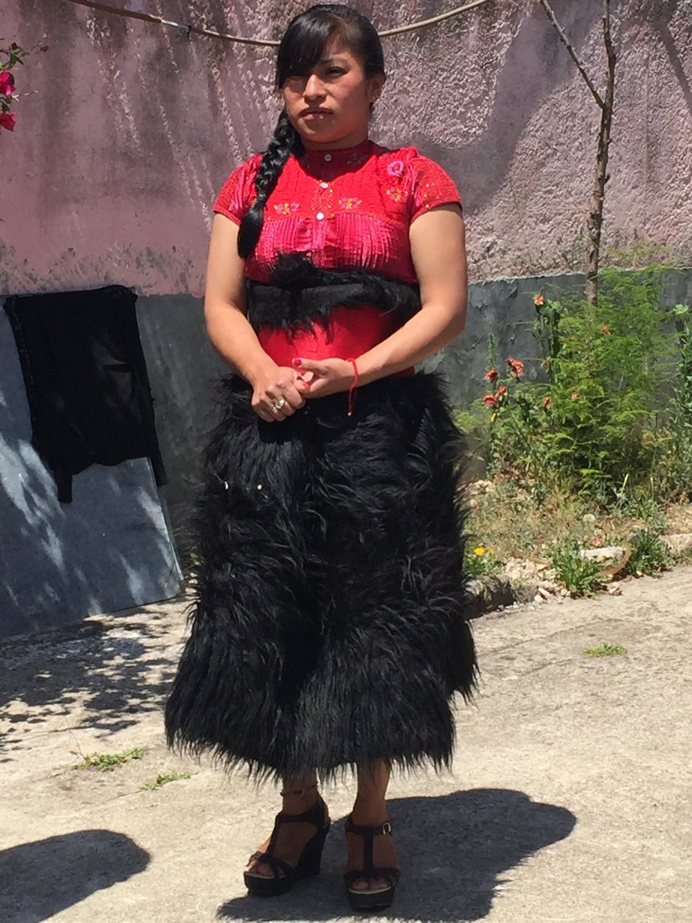 This is the typical dress of the women of Chamula. THer skirt is woven from black wool and then shredded to look like fur. A bright colored satin blouse along with a wide woven belt complete the look and are handmade locally.