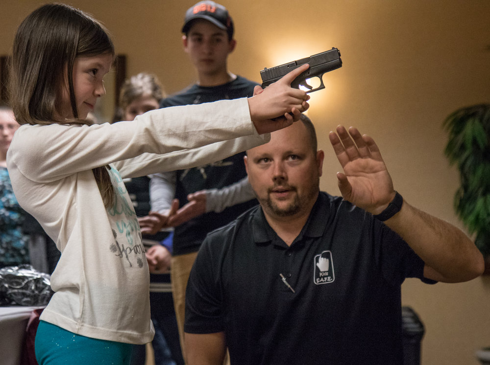 "LeBlanc observes a child handling a Glock handgun during a Kids S.A.F.E. course in Springfield, Ore., on Jan. 22, 2017, looking to ensure she keeps her finger off of the trigger, and the muzzle pointed in a direction away from anyone who would be harmed if the gun were to fire. ""With guns in the house comes a lot of responsibility,"" said LeBlanc. ""We've got to keep the kiddos safe. The only acceptable goal is zero firearm accidents."""