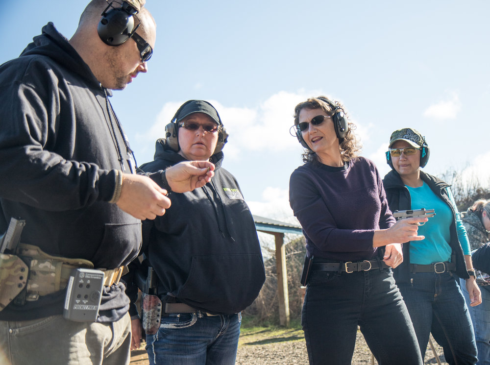 "Karen Wussting speaks with Derek LeBlanc about techniques for dealing with a misfiring gun during a women's self defense course at the Albany Pistol & Rifle Club in Albany, Ore., on Feb. 11, 2017. ""My goal is to get as many of these women as possible to feel comfortable carrying a firearm in their daily lives. It takes confidence, and confidence only comes with time and practice,"" said LeBlanc."