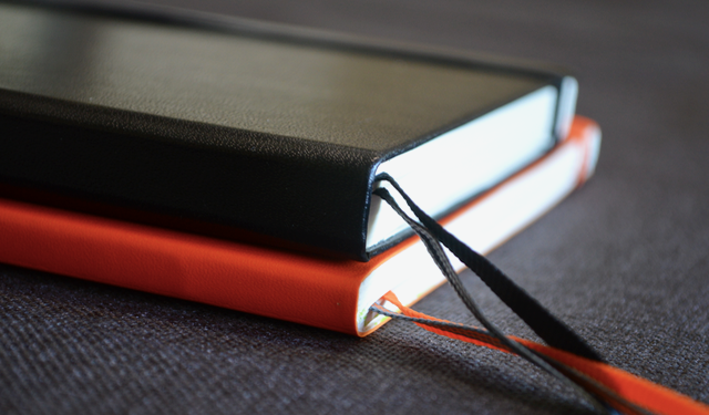 Composition Size Notebook (7x10in) shown in orange, A5 size (5.75x8.3in) notebook in black.