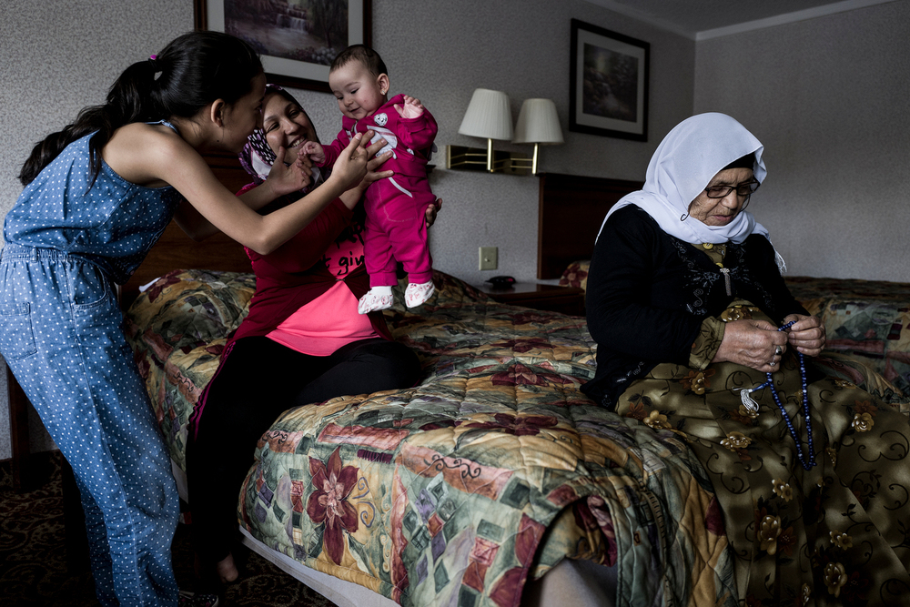 Ojleen Tanbal and her mother Najah, play with the Ojleen's younger sister, Maryam, while Ojleen's grandmother Maamo prays at a their hotel room, a day after arriving in the United States.