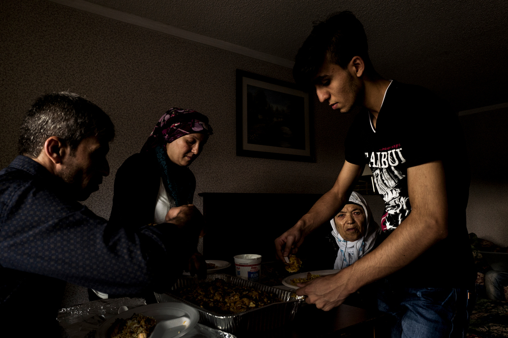 Muhammad Tanbal and his family eat dinner, donated from the Syrian community in Bloomfield Hills, at their hotel a day after they arrived in the states. A meal of rice, chicken, and yogurt, is somewhat of staple for the family and a common Syrian dish.