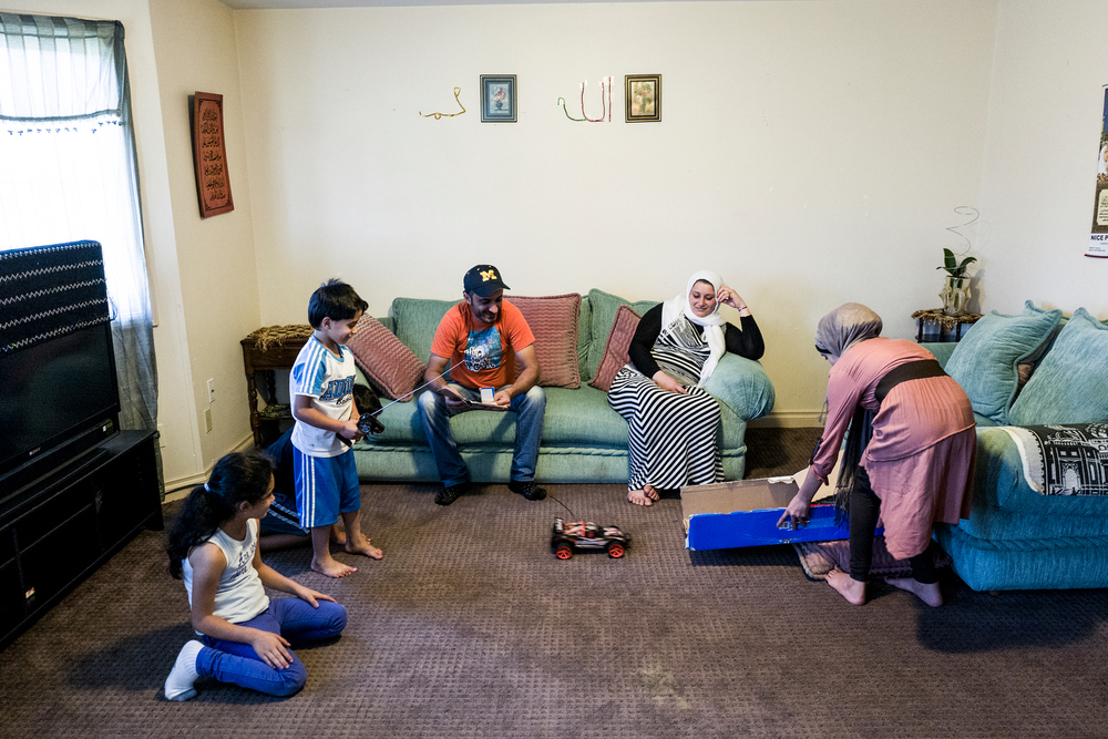 "The Al-Zoobi family spends time together in their home. They fled Syria three years ago, and have lived in the United States for four months. ""I didn't know if bombs would come out of nowhere and kill my children,"" said Louai Al-Zoobi. (third from left). His son has a learning disability which he thinks will be better treated in America."