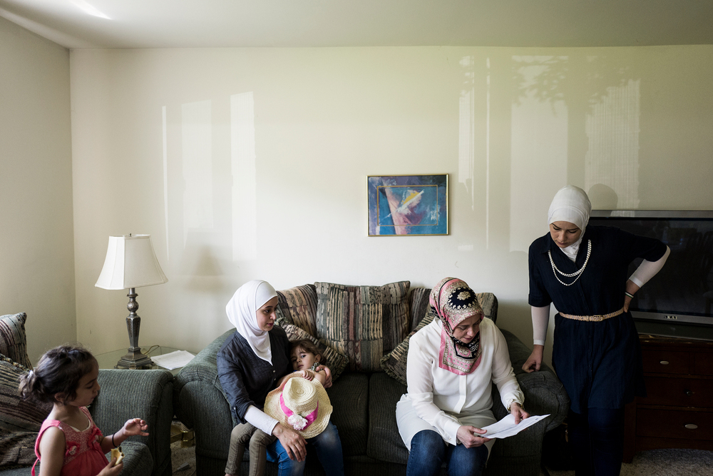 Rasha Basha, a Syrian volunteer in Bloomfield Hills, goes over medical paperwork with Raeda Al Hayek, at the Al Hayek's new home.