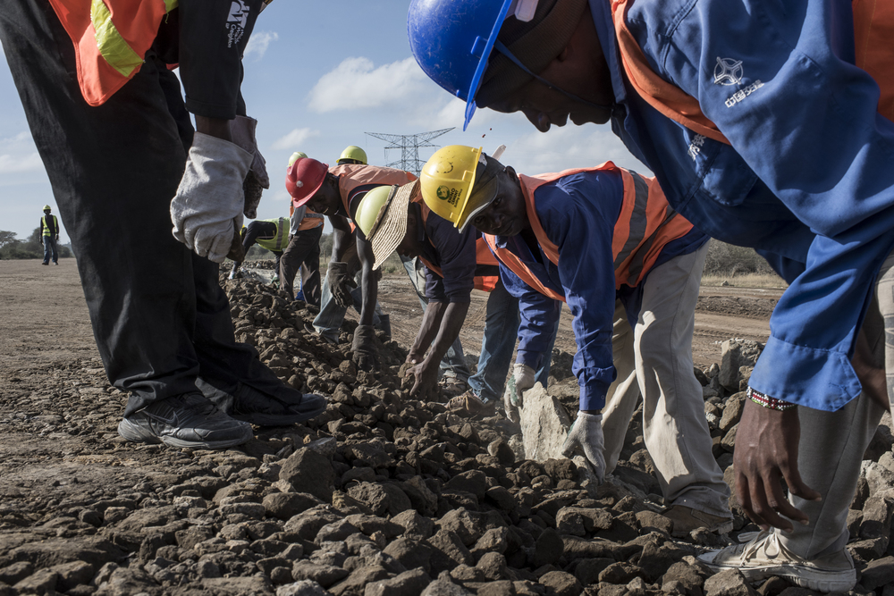 Workers for the China Road and Bridge Corporation move stones for the construction of the new Standard Gauge Railway just outside the eastern fence line of Nairobi National Park in Nairobi, Kenya on March 20, 2016.