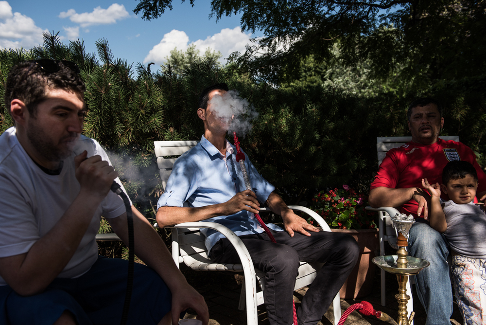 Badi Dabjan, a volunteer in the Syrian community and asylum seeker, smokes hookah with Nedal Al Hayek and Thaer Hoshan, both refugees from Daraa, Syria, at a community potluck. The gathering was an opportunity for many of the new refugee families to meet one another for the first time.