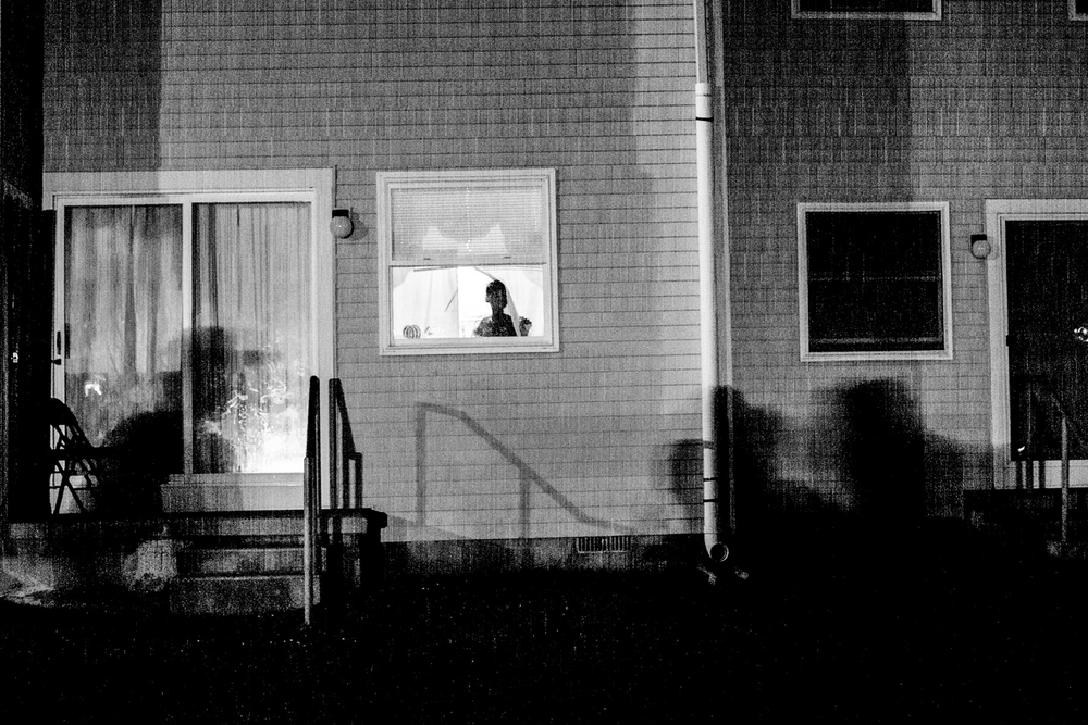 USA. Atlantic City, New Jersey. July 14, 2012 : A young girl looks out of a window of her home in the Back Maryland neighborhood of Atlantic City, a section of the city struck with recent violence. Residents fear leaving their homes at night because of the violence in their neighborhood.