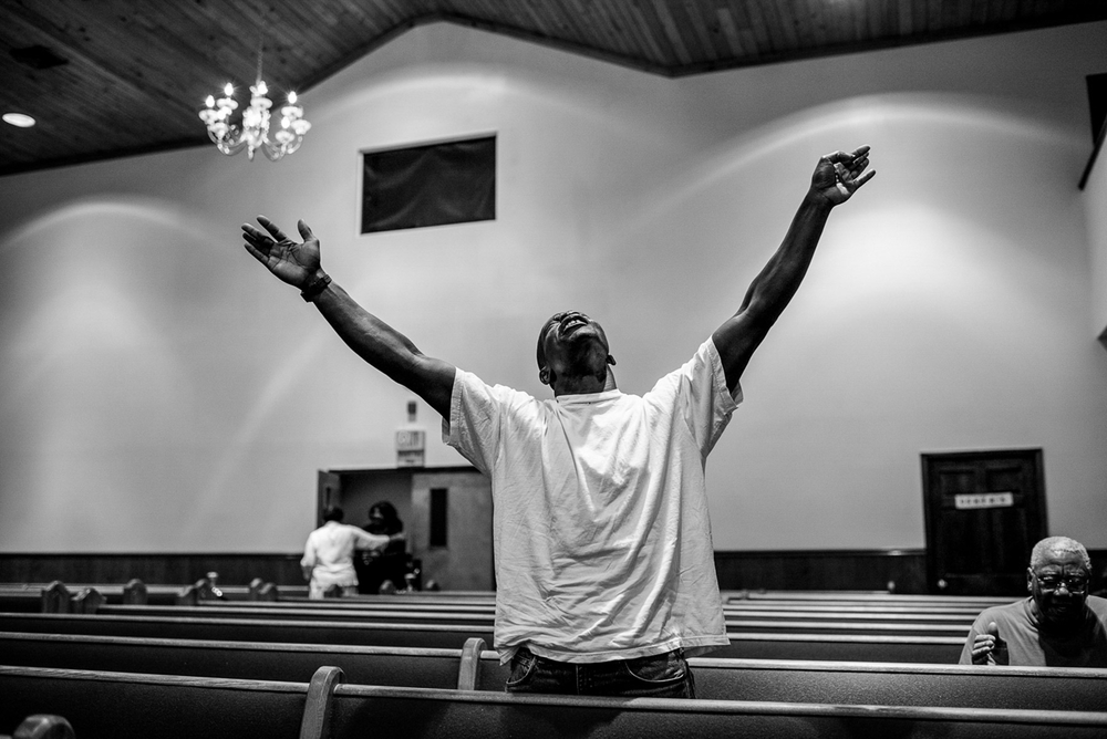 USA. Charleston, South Carolina. June 19, 2015: Oscar Mitchell, from North Charleston, prays for peace at Gethsemane Baptist Church on Romney Street, a cross street with on King Street in Charleston, South Carolina, two days after the racially motivated shooting at Emanuel AME Church which left nine people dead.