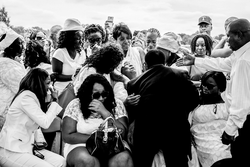 USA. Wilmington, Delaware. July 21, 2012 : Family members weep as the casket of Alexander Kamara is lowered into the ground. Kamara, 16, was a promising student and soccer player who was killed after being caught in the crossfire of a shooting that took place on a Sunday afternoon during a soccer game in Wilmington.