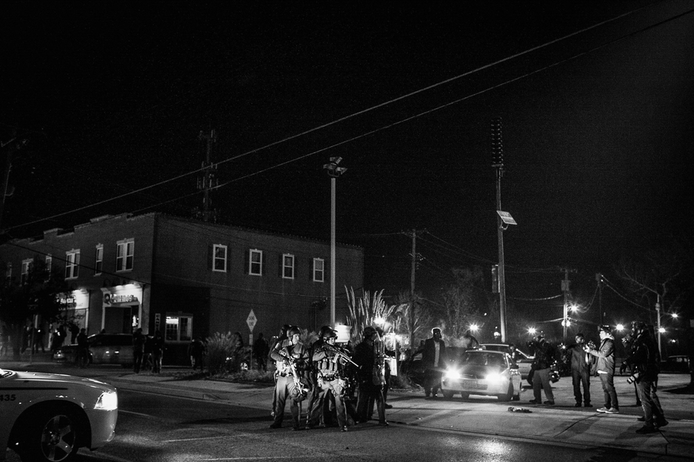 USA. Ferguson, Missouri. November 26, 2014 : Police officers take control of the street after making an arrest as protestors became violent a day after the non-indictment decision in the shooting death of Michael Brown. Brown, 18, was shot in killed in a officer involved shooting. His death caused unrest in Ferguson and became symbolic in the Black Lives Matter movement throughout the United States.