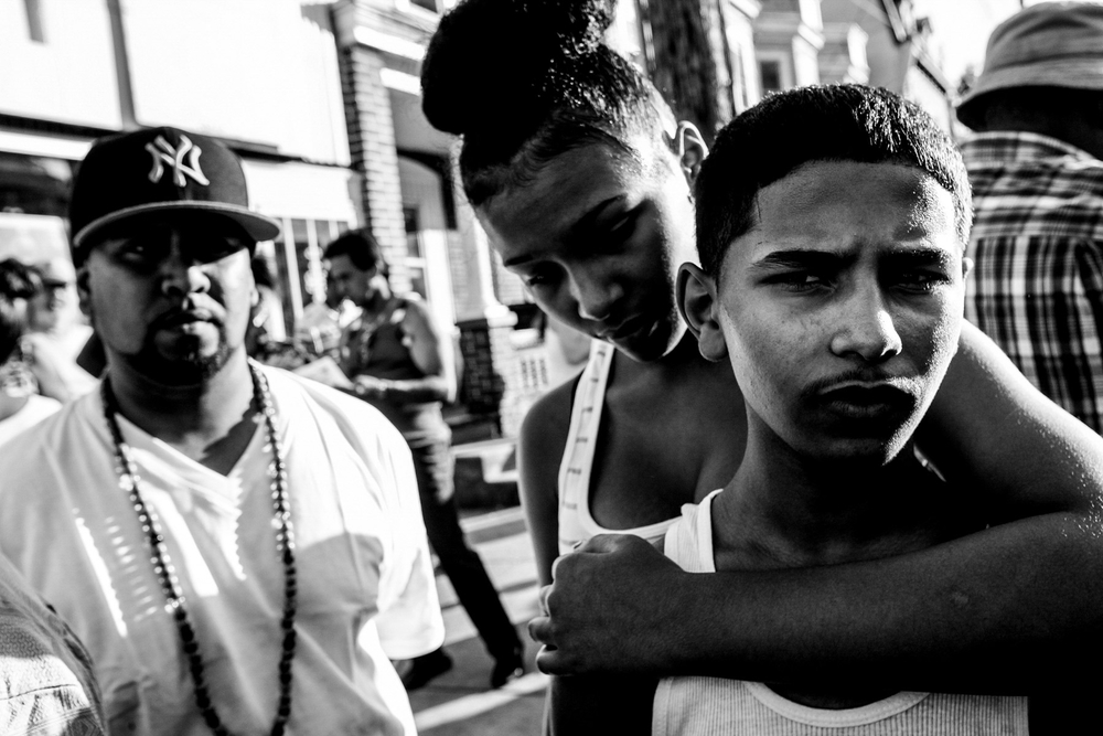 USA. Wilmington, Delaware. August 11, 2011 : Brooklynn Bailey, 13, of Wilmington, hugs Nasser Alradaer, Norman Alhout's 14-year-old nephew. Alradaer, was close with his uncle before he was murdered inside his grocery store in the Browntown neighborhood of Wilmington.