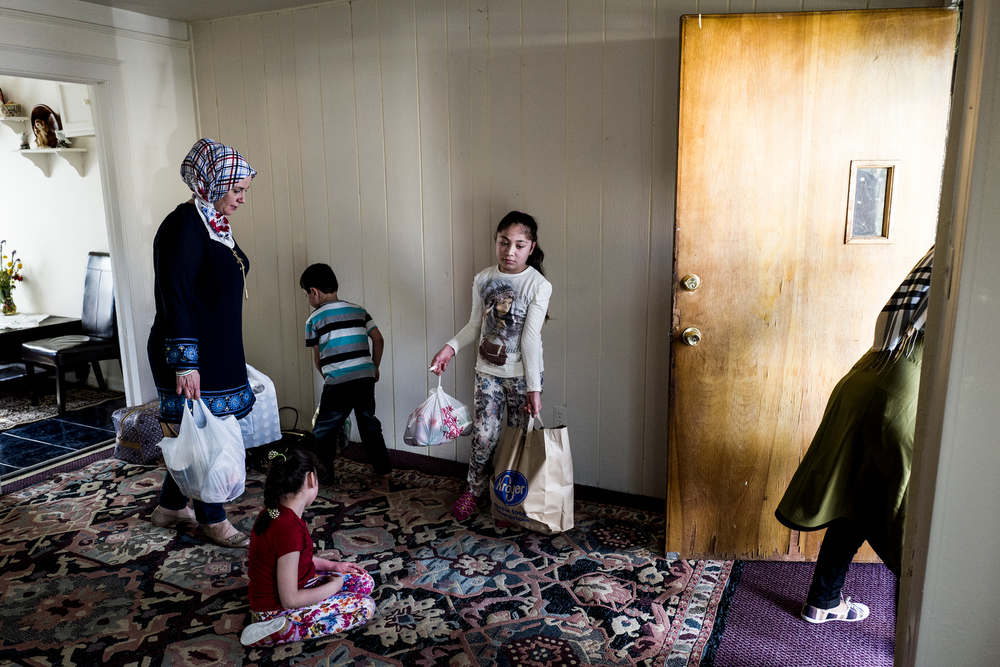 The Haji Khalif family carries their belongings out of their first placement home. The Kurdish family of five moved here from their first placement home in Dearborn due to their daughter's disability. They originally fled their own home in Aleppo and lived in Jordan before coming to the United States.