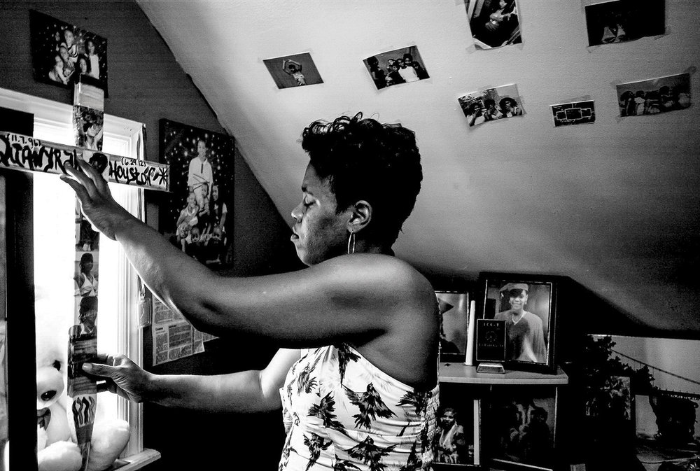 USA. Camden, New Jersey. June 27, 2013 : Montika Lowe puts the memorial cross for her daughter Qua'Nyrah Houston back on the window sill of Qua'Nyrah's room. Houston, 15, was killed in a firebombing in Camden along with her 16-year-old boyfriend. No one has been charged in the killing.