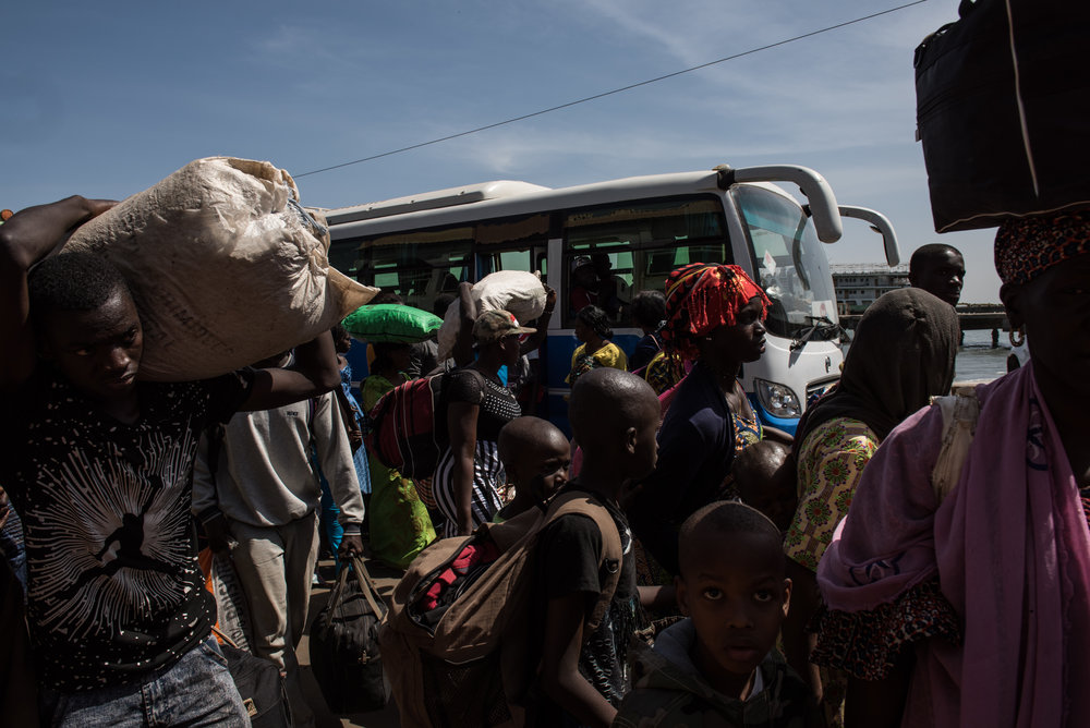 Families who fled the country wait to board buses after returning home a day after authoritarian ex-president Yahya Jemmeh left the country, on January 22, 2017 in Banjul, The Gambia. Jammeh was defeated by the current president, Adama Barrow, ending his 22 year rule.