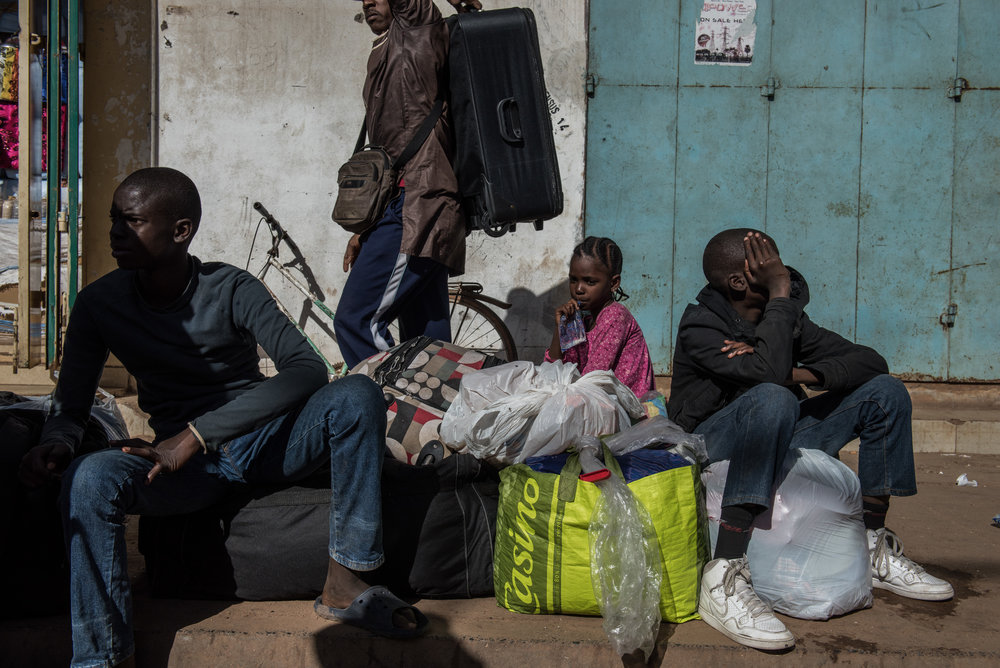 THE GAMBIA. Banjul. January 23, 2017. Ulhaji Sesay, 14, his sister, Fatemahta, 6, and brother, Jibril, 12, wait for their mother outside the Banjul Ferry Terminal after returning home on January 23, 2017 in Banjul, The Gambia. The family had not been to school in one month since fleeing the country.
