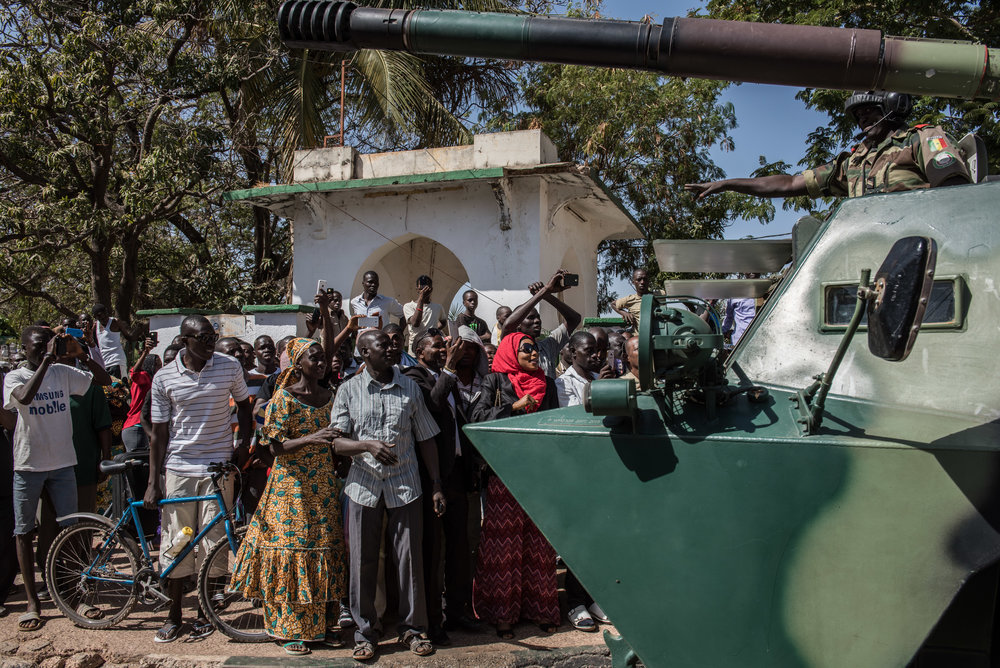 People cheer as ECOWAS (Economic Community of Western Africa States) troops from Senegal gather outside the Gambian statehouse on January 23, 2017 in Banjul, The Gambia. ECOWAS is in Gambia to ensure a safe transition of power after authoritarian ruler Yahya Jammeh left the country two days prior, admitting defeated to the current president, Adama Barrow.
