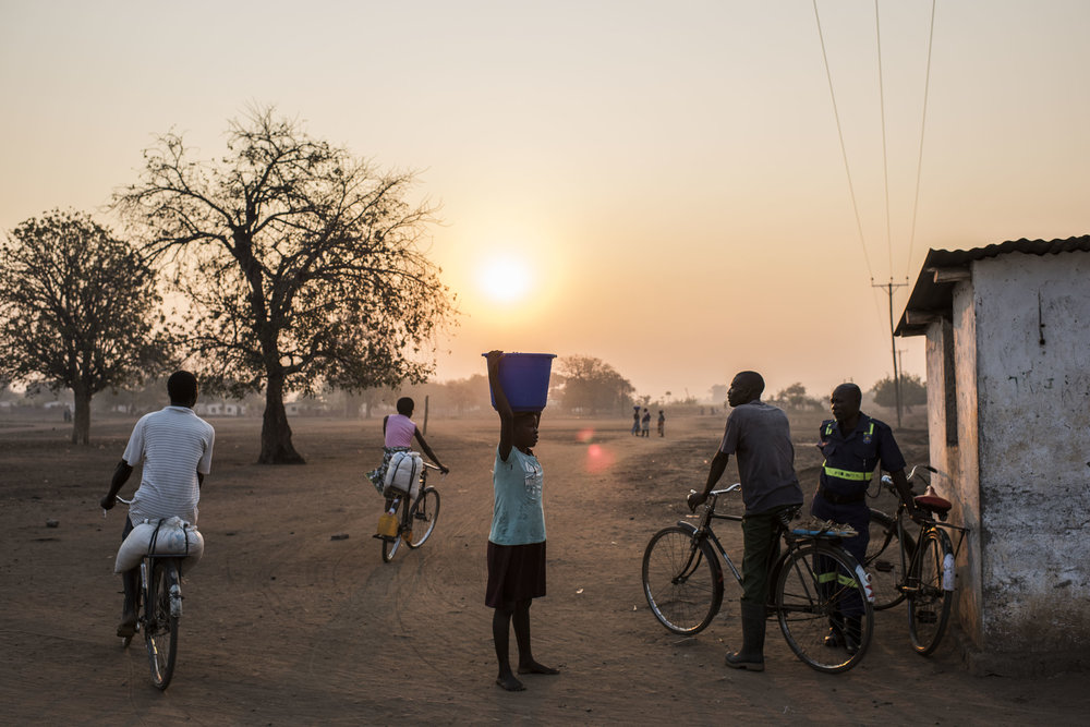 People walk and cycle in the village of Malikopo, which lies in one of the areas most affected by drought, on September 9, 2016 in Chikwawa, Malawi.