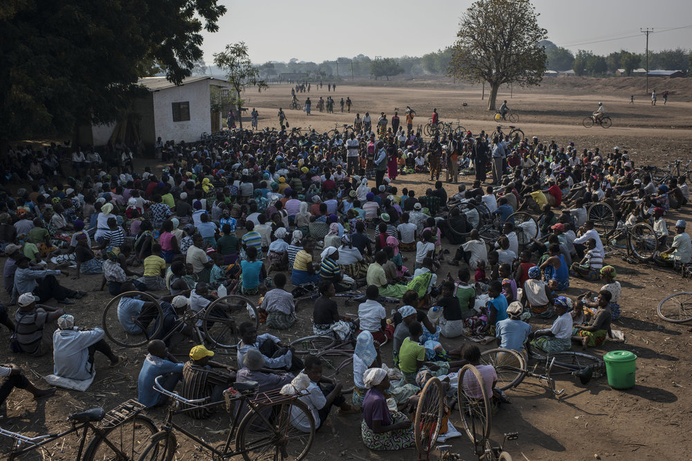 Men and women listen to a briefing on the food distribution process outside a school in the village of Malikopo, which lies in one of the areas most affected by drought, on September 9, 2016 in Chikwawa, Malawi.