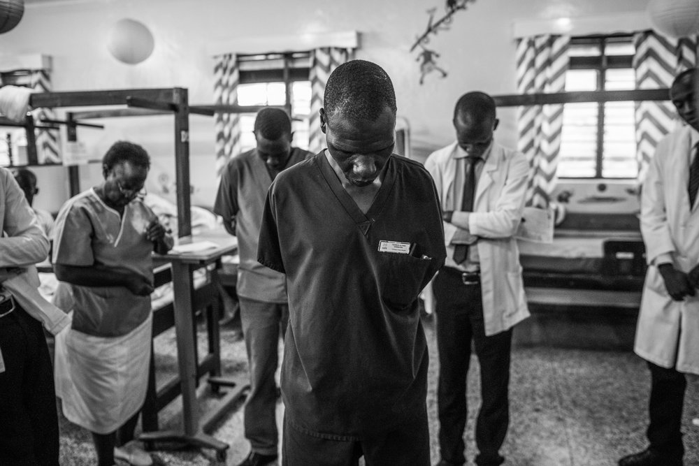 Hospital staff pray to start the day at Cure Hospital on February 6, 2017 in Mbale, Uganda.