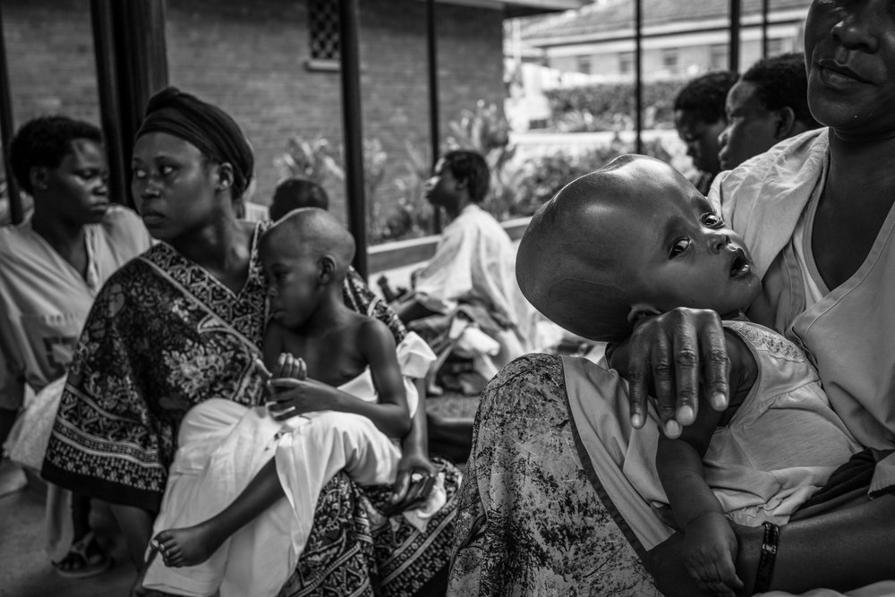 Mothers gather with their children on the compound of Cure Hospital on February 4, 2017 in Mbale, Uganda. Some mothers are repeat visitors to this hospital and have returned because of an infection or a problem with a shunt in their child's head. One woman said fellow villagers thought she had practiced witchcraft after her baby was born with such a deformity.