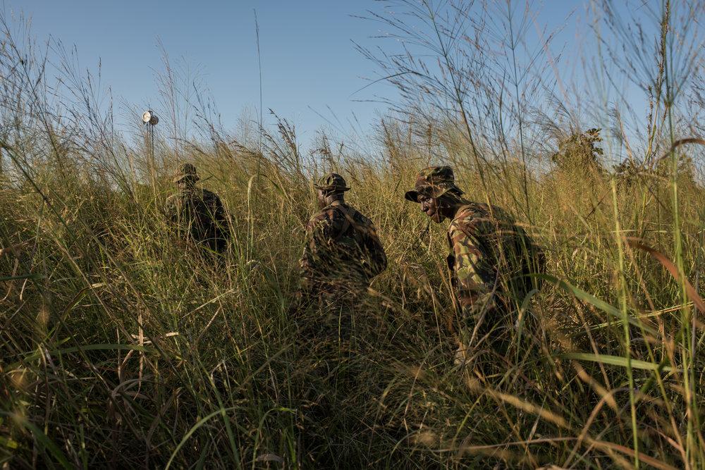 Rangers walk through tall grass during a recon patrol near the Bagunda outpost in Garamba National Park on November 28, 2017.