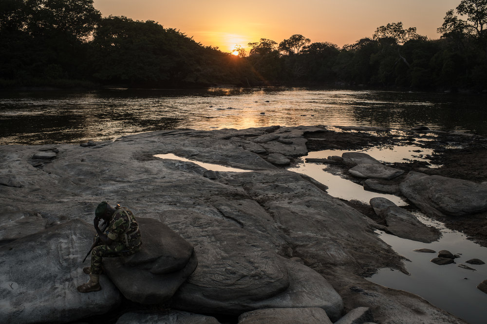 A ranger rests at the bank of the Dungu river during a tour of Garamba National Park on November 26, 2017.