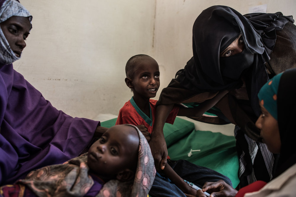 Abdullahi Mohamud, 5, cries next to his mother Sahro Mohamed Mumin, 30, and brother, Abdulrahman Mahamud, 2, as a nurse struggles to find a vein for an injection at a government run health clinic on February 25, 2017 in Shada, Somalia. Abdullahi was diagnosed with bronchitis, Abdulrahman with pneumonia. Both children were also suffering from severe malnutrition.The family lost all of their animals due to drought and had traveled 150 kilometers in search of a better situation.