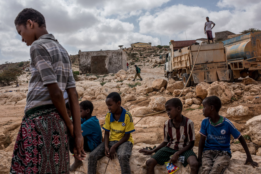 Boys watch as water is pumped from a nearly dried up riverbed on February 24, 2017 in Dhudo, Somalia.