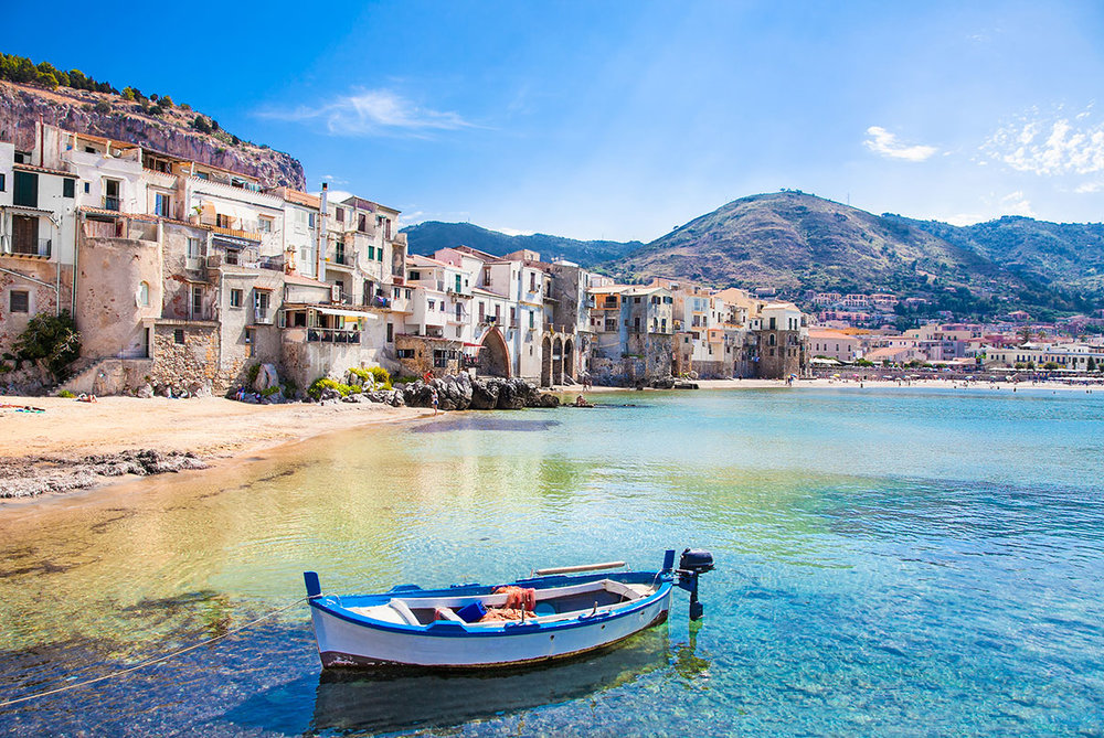 Old-harbor-with-wooden-fishing-boat-in-Cefalu-Sicily.jpg