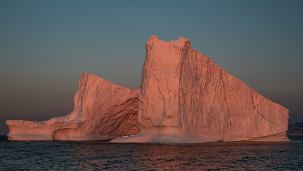 shadow of our boat at the bottom of the iceberg during sunset