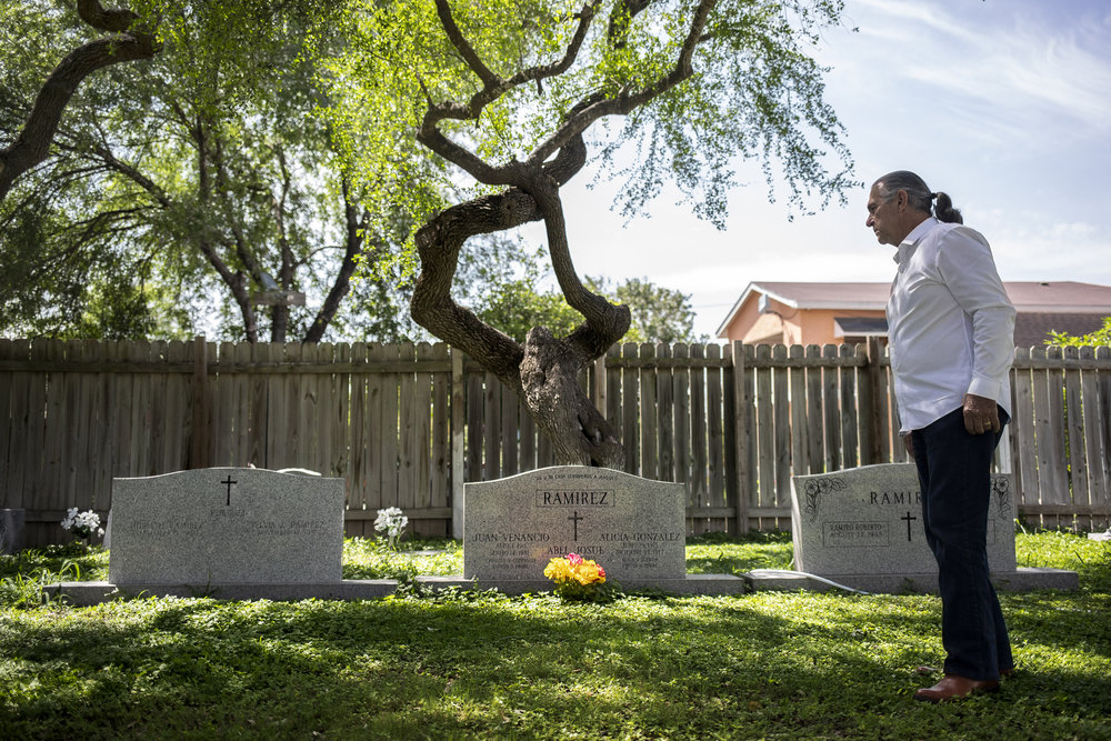 Ramiro Ramirez looks at the graves of his parents and the headstone for hiomself and his wife at the Jackson Chapel Cemetary in San Juan, TX.