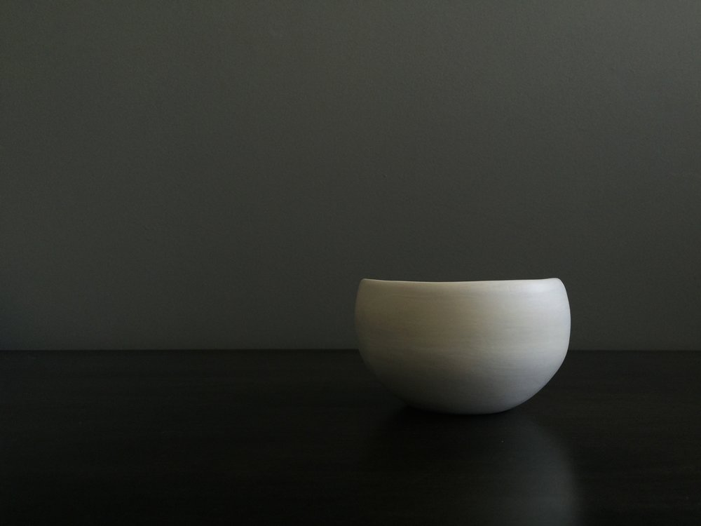 white porcelain bowl in simple form on modern background by esselhaus