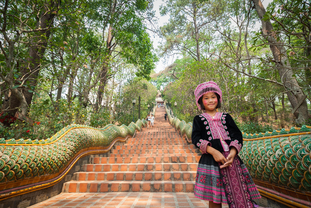 Young girl stands on the bottom of the 309 steps in Wat Phra That Doi Suthep. One of the most important temples in Thailand.  Chiang Mai, Thailand